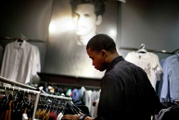 In this Wednesday, Dec. 12, 2012 photo, Dominic Plummer, of Atlanta, shops in an H&M store, in Atlanta. The Federal Reserve reports how much consumers borrowed in December on Thursday, Feb. 7, 2013.  (AP Photo/David Goldman) Photo: David Goldman