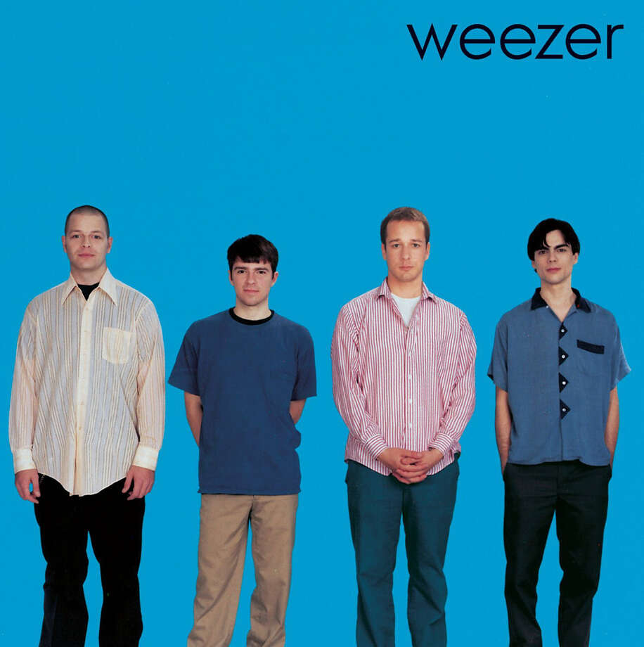 """Weezer –- """"Weezer (The Blue Album):Critics agree this debut album is one of the top records of the 1990s, and in 2002 readers of Rolling Stone ranked the album the 21st greatest of all time. If you're a longtime Seattleite, you may remember that in fall 1994, the band was scheduled for an in-store performance at the Tower Records at Fifth Avenue North and Mercer Street, which is where the QFC is now. They ended up not playing, but stayed around for hours signing autographs and talking with the roughly 350 fans who showed up. Can you imagine if Weezer did that now? The record store would be packed. (Album cover)"""