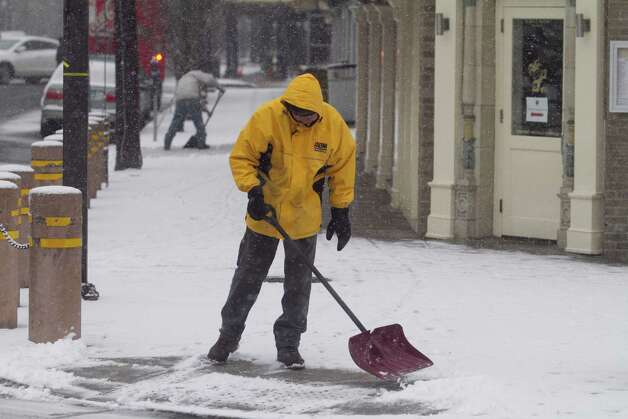A Downtown Special Services District employee shovels a sidewalk on Bedford Street in Stamford, Conn. on Friday, Feb. 8, 2013. Photo: Chris Preovolos / 2011