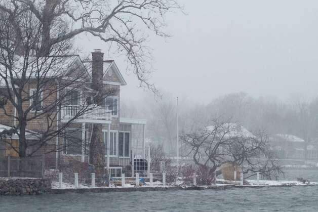 Icy water is perilously close to homes on Holly Pond on the Stamford-Darien border on Friday, Feb. 8, 2013. Photo: Chris Preovolos / Stamford Advocate