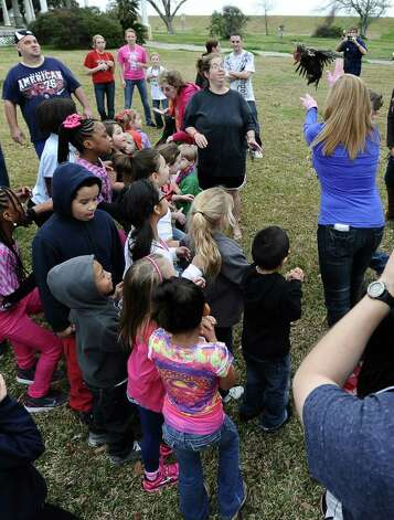"Patricia ""Tecoo"" Saucier Leger tosses the chicken that starts the courir parade down Lakeshore Drive in front of many excited children on Thursday, February 7,2013, in Port Arthur. Photo taken: Randy Edwards/The Enterprise Photo: Randy Edwards"