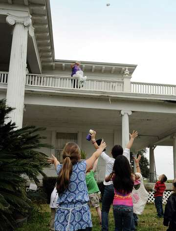 Families stand below the balcony of the Rose Hill Manor in Port Arthur collecting beads and waiting in anticipation for the courir parade down Lakeshore Drive on Thursday, February 7,2013. Photo taken: Randy Edwards/The Enterprise Photo: Randy Edwards