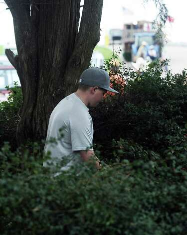Twelve year old Trevor Kimbell, from Bridge City, searches for the courir parade chicken in the bushes in front of the Rose Hill Manor on Thursday, February 7,2013, in Port Arthur. Photo taken: Randy Edwards/The Enterprise Photo: Randy Edwards