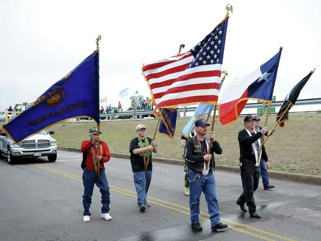 The American Legion carry flags as they walk along the parade route during the Courir Parade on Thursday, February 7,2013, in Port Arthur. Photo taken: Randy Edwards/The Enterprise