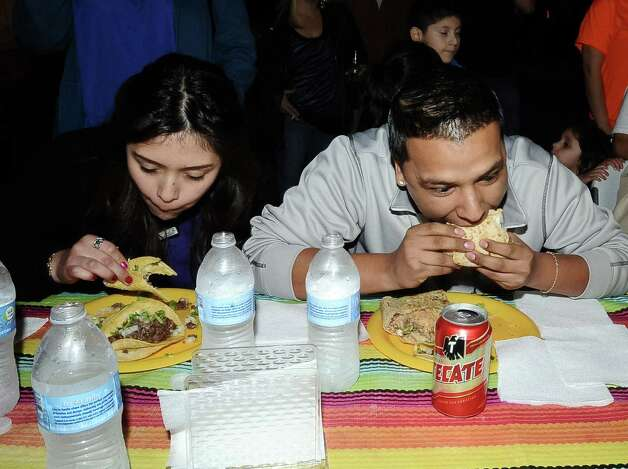 Cricthian Herrera, left, and Daniel Romero, right, compete in the couples eating contest at Tacos La Bama's First Thursday event on Thursday, February 7, 2013. Photo taken: Randy Edwards/The Enterprise Photo: Randy Edwards