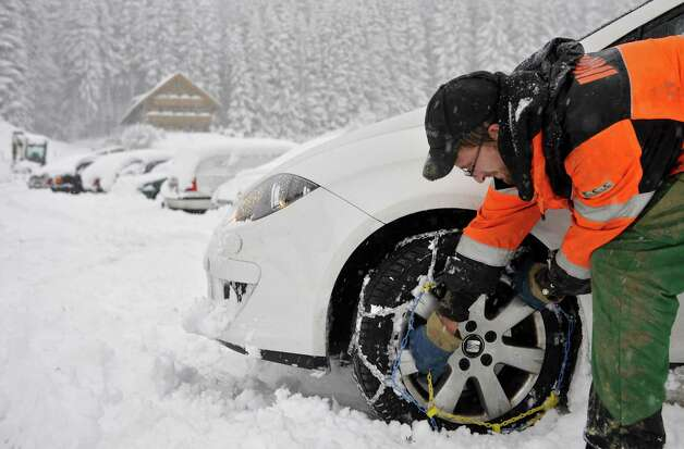 A man attaches snow chains to the wheels of his car near the southern German town of Oberstaufen on December 11, 2009. Heavy snowfall was reported in the southern part of the country. AFP PHOTO DDP /  JOERG KOCH  GERMANY OUT (Photo credit should read JOERG KOCH/AFP/Getty Images) Photo: JOERG KOCH, AFP/Getty Images / 2009 AFP
