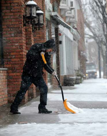 Juan Panchana shovels in front of Colony Grill in downtown Fairfield, Conn. on Friday, Feb. 8, 2013. Snow was falling steady as the National Weather Service reports that southern Fairfield County could get 10 to 14 inches by time the storm passes. Photo: Cathy Zuraw / Connecticut Post