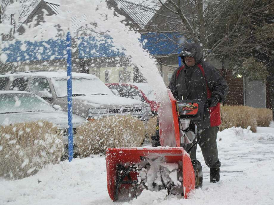 A worker blows snow out of a parking lot on Burtis Avenue during the winter storm Nemo. Feb. 8, 2013, New Canaan, Conn. Photo: Tyler Woods