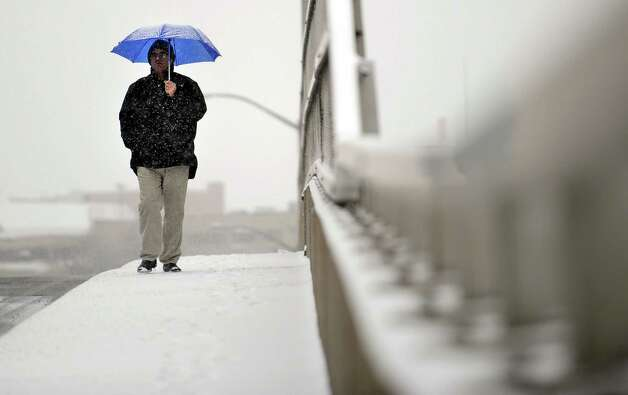 A man walks down Bridge Street in Shelton, Conn. Friday, Feb. 8, 2013 as the predicted blizzard begins to blanket