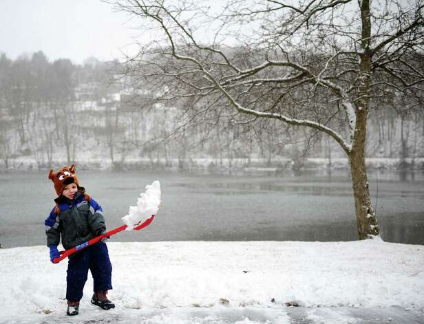 Four-year-old Derick Mullin helps shovel the driveway Friday, Feb. 8, 2013 in Derby, Conn. as the predicted blizzard begins to blanket the state. Photo: Autumn Driscoll