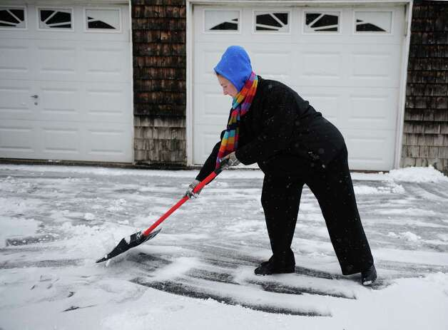 Ashley Piasecki shovels her driveway Friday, Feb. 8, 2013 in Derby, Conn. as the predicted blizzard begins to blanket the state. Photo: Autumn Driscoll