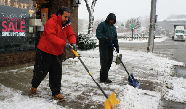 Jose Flores, left, and Fabian Treto shovel the sidewalk on Post Road Easy in front of Klaff's of Westport early Friday as the leading edge of a predicted blizzard moved into town. WESTPORT NEWS, CT 2/8/13 Photo: Paul Schott / Westport News