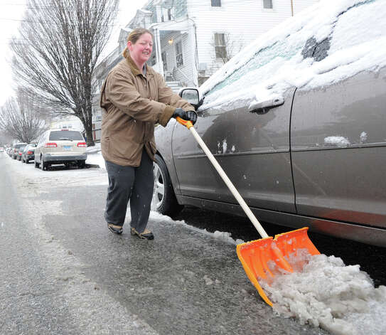 LeAnn Hinkle clears snow from around her car on South Water Street during the snowstorm that hit the Byram section of Greenwich, Conn., Friday, Feb. 8, 2013. Hinkle is an art teacher for the Greenwich Public Schools and had the day off due to the storm. Photo: Bob Luckey / Greenwich Time