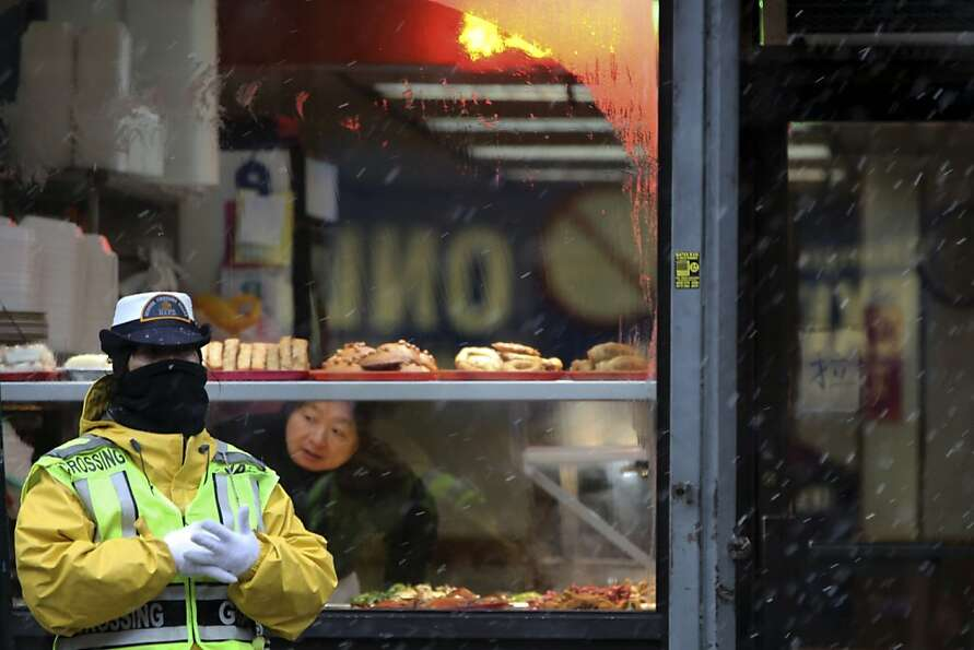 A crossing guard takes cover from the snow under the awning of a restaurant in New York's Chinatown,