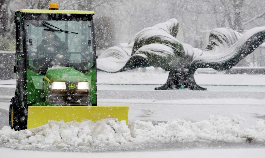 Kevin Quick plows a slushy mix in front of M & T Bank during a winter storm in Buffalo, N.Y., Friday, Feb. 8, 2013. In some upstate areas, snow fell early Friday morning and was expected to increase throughout the day, with the heaviest accumulations expected in eastern New York on Friday night. Photo: AP