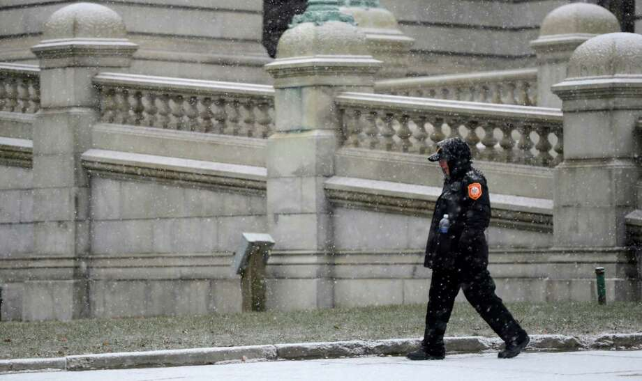 A traffic enforcement officer walks through the snow that has started to cover untreated surfaces near the Capitol building this morning Feb. 8, 2013, as a forecasted storm approaches Albany, N.Y.   (Skip Dickstein/Times Union) Photo: SKIP DICKSTEIN