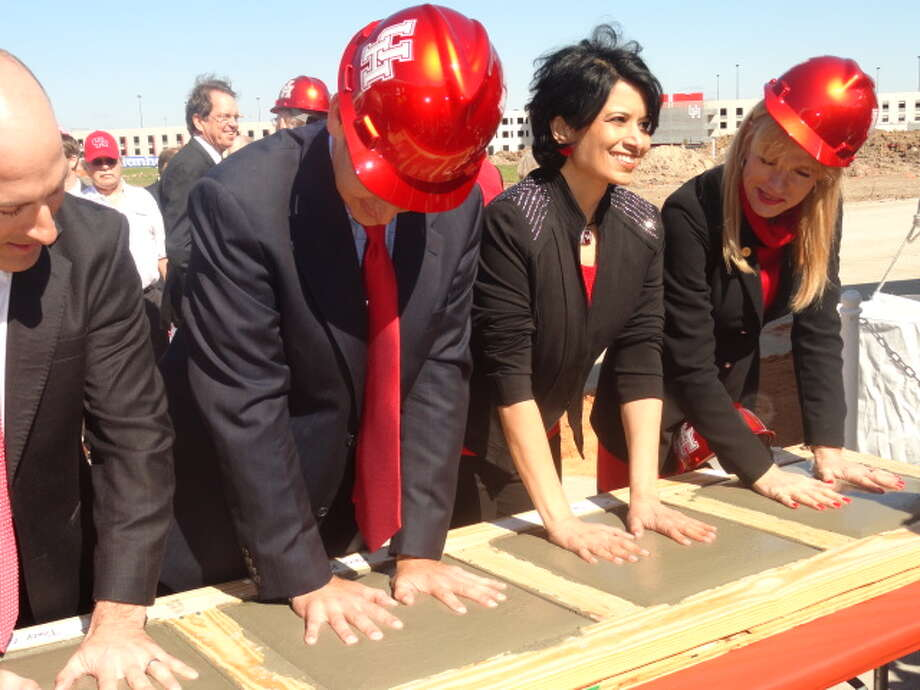 UH president Dr. Renu Khator puts her hands in concrete that will be on display at the new stadium.