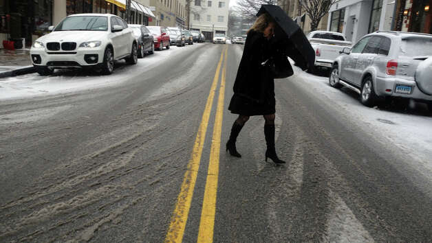 A woman battles her umbrella crossing Lewis Street as a blizzard moves into Greenwich, Conn., Feb. 8, 2013. Photo: Keelin Daly / Keelin Daly