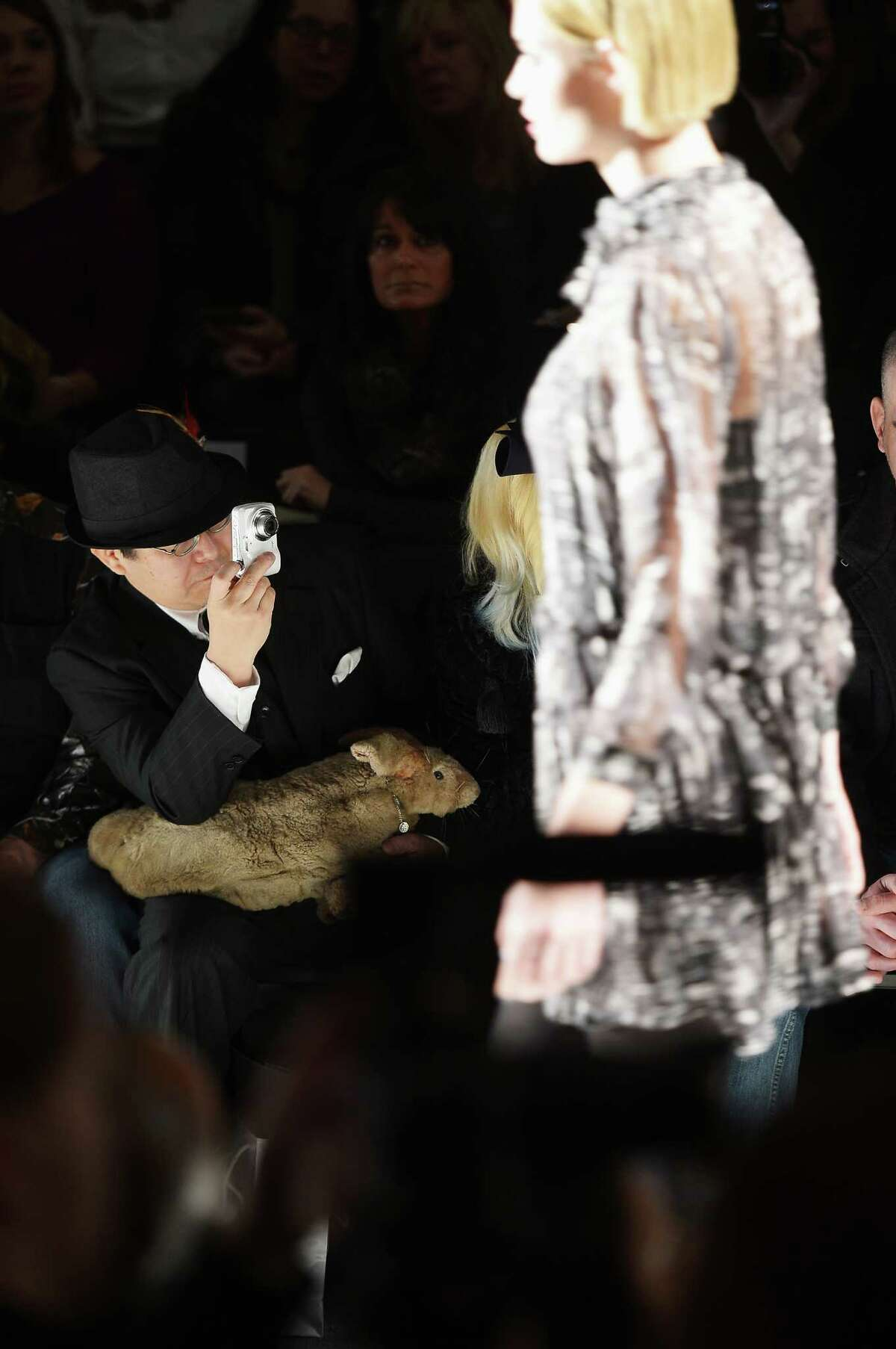 Taxidermist Takeshi Yamada is holding a stuffed rabbit that has been equipped with what appears to be webbed feet, front row at New York Fashion Week.