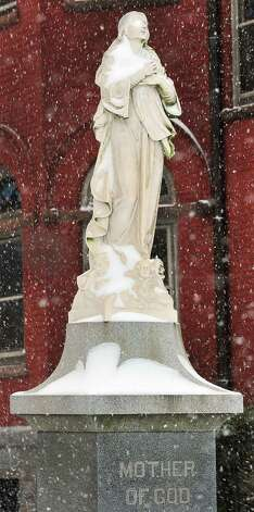 A statue of Mary, Mother of God, appears to pray for the end of the snow outside St. Peter's Rectory in Danbury Friday, Feb. 8, 2013. Photo: Michael Duffy / The News-Times