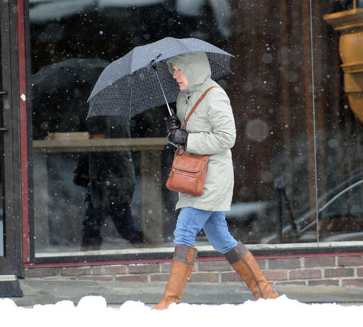 A woman shields herself with an umbrella while walking on East Putnam Avenue during the snowstorm that hit Greenwich, Conn., Friday, Feb. 8, 2013. Photo: Bob Luckey / Greenwich Time