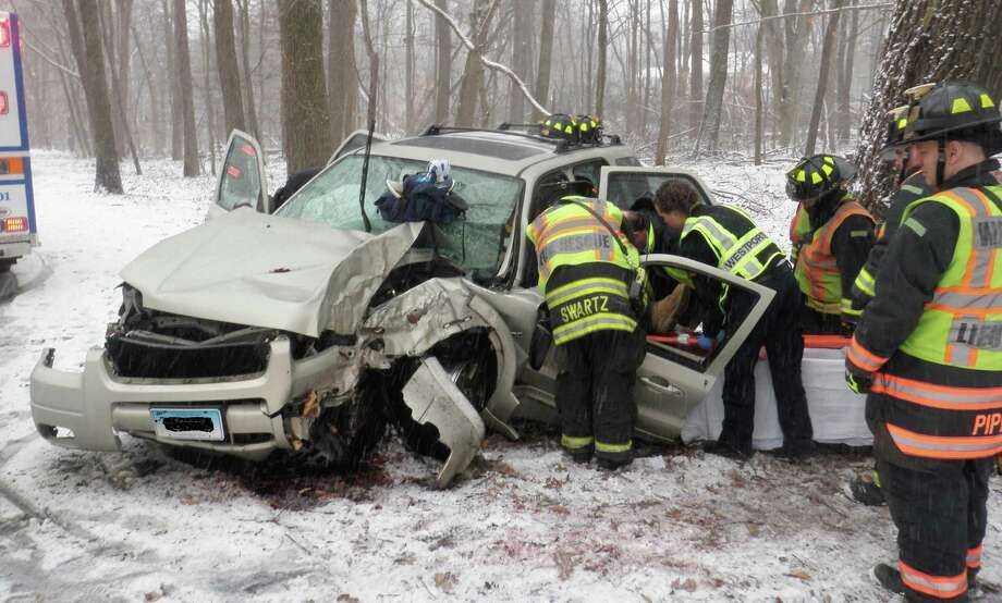 Westport firefighters assist the injured driver of an SUV that skidded off the snow-slick Merritt Parkway and crashed into a tree Friday morning.  WESTPORT NEWS, CT 2/8/13 Photo: Westport Fire Department / Westport News contributed