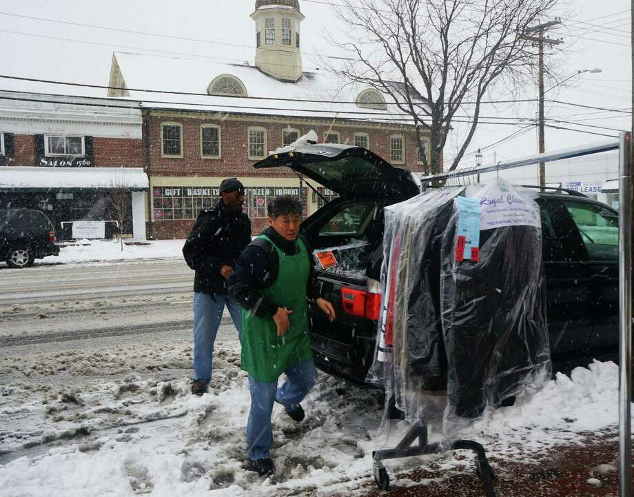 "Maurice Blackwood , rear, picks up drycleaning during Friday's storm for an upcoming business trip. He said the owners of Royal Cleaners did him a ""huge favor"" staying open until he got there. Photo: Genevieve Reilly / Fairfield Citizen"