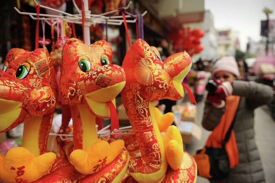 A woman takes pictures of toy snakes at a market in Shanghai on February 6, 2013 ahead of the Lunar New Year. Preparations continue for the Lunar New Year which will celebrate the Year of the Snake on February 10.    AFP PHOTO / Peter PARKSPETER PARKS/AFP/Getty Images Photo: PETER PARKS, Staff / AFP