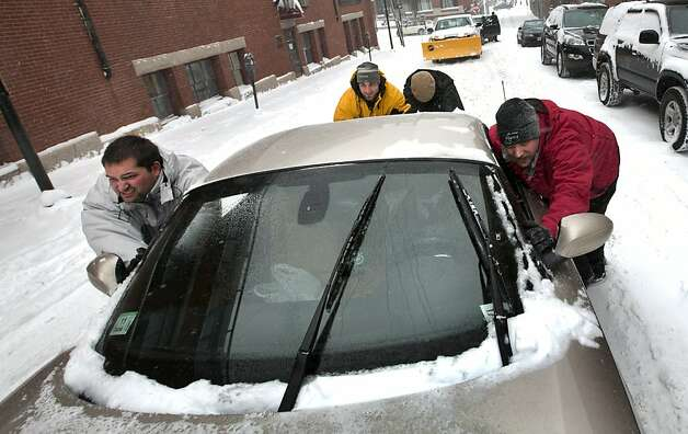 A group of men help push a sports car up a snow-covered street in the Old Port section of Portland, Maine, during a snow storm, Friday, Feb. 8, 2013. The storm is expected to dump up to two feet of snow on the region. Photo: Robert F. Bukaty, Associated Press