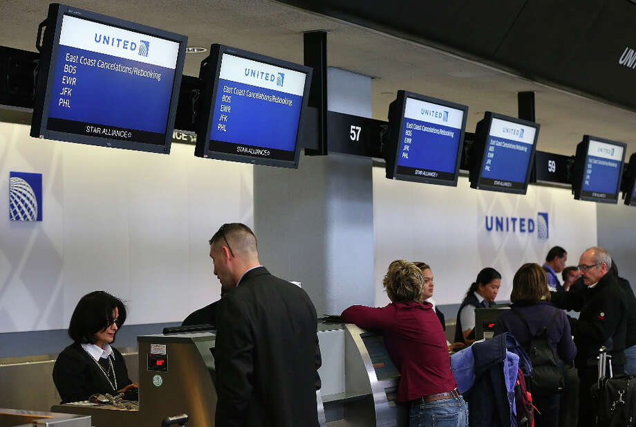 United Airlines ticket agents help customers rebook flights that were canceled due to weather at San Francisco International Airport on February 8, 2013 in San Francisco, California.  Thousands of flights to the East Coast were canceled as a potentially historic blizzard is set to dump up to three feet of snow in the Northeast from New York City to Boston. Photo: Justin Sullivan, Getty Images / 2013 Getty Images