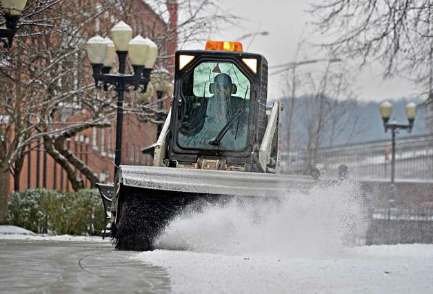 Grounds keeper Doug Gleason uses a bobcat to sweep snow from the walkways at Russell Sage College in Troy Friday afternoon Feb. 8, 2013.  (John Carl D'Annibale / Times Union) Photo: John Carl D'Annibale / 00021096A