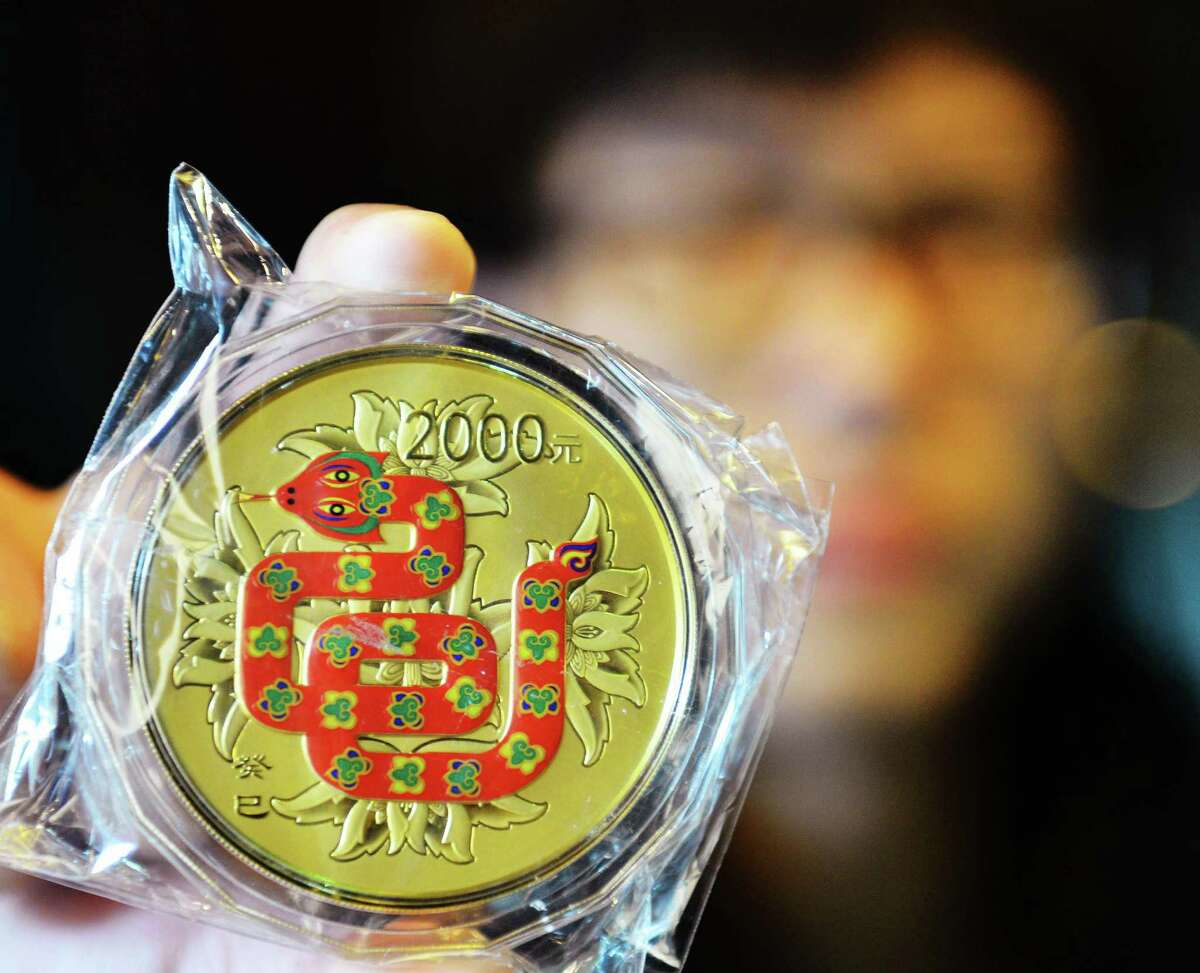 This picture taken on February 7, 2013 shows a salesman showing a gold coin with a snake image on it to mark the coming year of snake in a gold shop in Hangzhou, east China's Zhejiang province. All Chinese people arround the wolrd will welcome the Year of Snake that would come on February 10 this year until the Lantern festival. CHINA OUT AFP PHOTOSTR/AFP/Getty Images