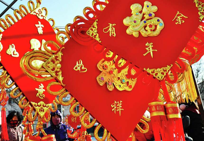 This picture taken on February 7, 2013 shows people buying lunar new year decorations with the word