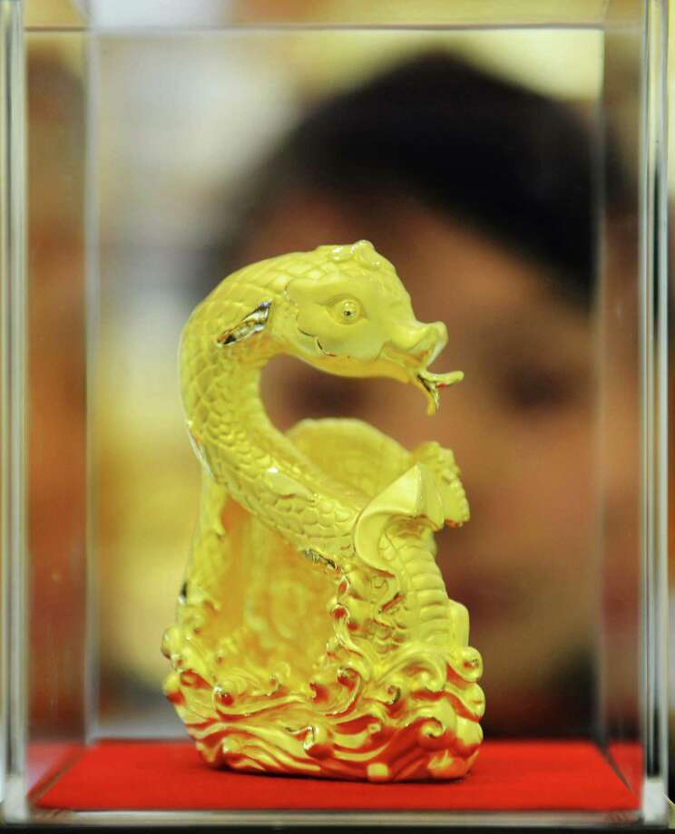 This picture taken on February 7, 2013 shows a gold snake sculpture, which is made to mark the coming year of the snake, on display at a gold shop in Hangzhou, east China's Zhejiang province.  The lunar new year, or spring festival, falls on February 10. CHINA OUT   AFP PHOTOSTR/AFP/Getty Images Photo: STR, AFP/Getty Images / AFP