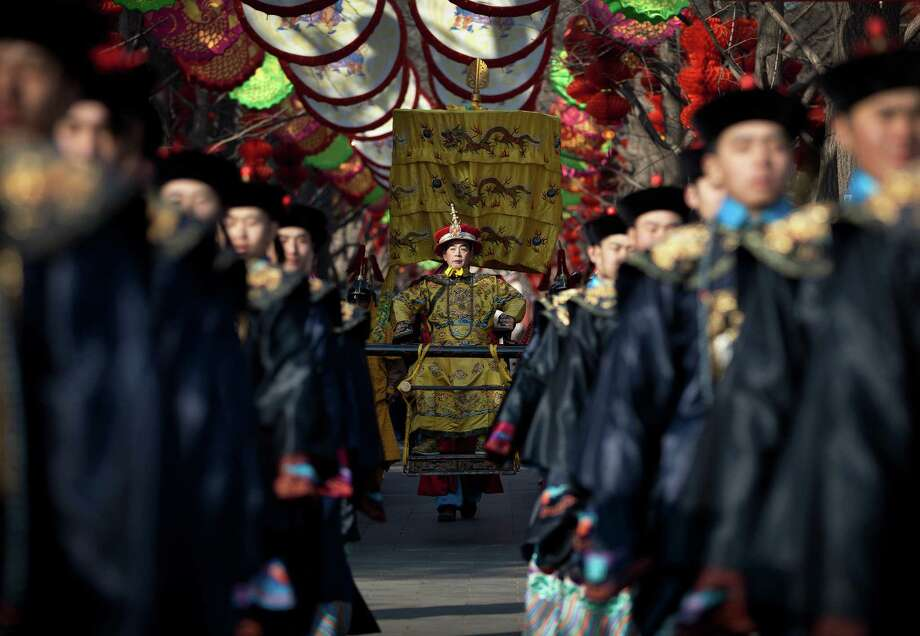 A Chinese actor dressed as Qing Dynasty emperor, center, sits on a sedan chair during a rehearsal of an ancient Qing Dynasty ceremony ahead of the upcoming Chinese New Year at Ditan Park in Beijing Friday, Feb. 8, 2013. Chinese will celebrate the Lunar New Year on Feb. 10 this year which marks the Year of Snake. Photo: Andy Wong, AP / AP