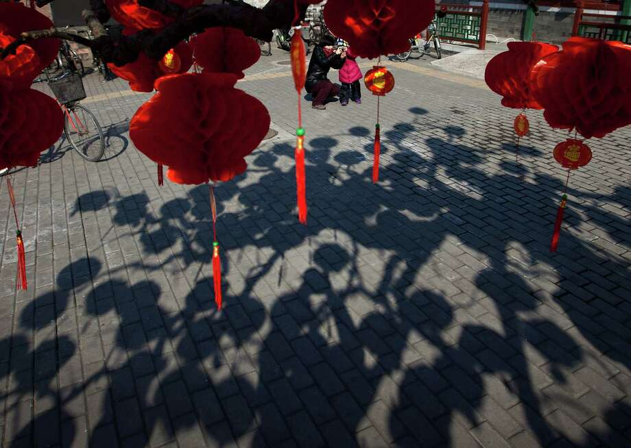 A Chinese woman helps her child to snap pictures near a tree decorated with red lanterns ahead of Chinese New Year celebrations at Ditan Park in Beijing Friday, Feb. 8, 2013. Chinese will celebrate the Lunar New Year on Feb. 10 this year which marks the Year of Snake. Photo: Andy Wong, AP / AP