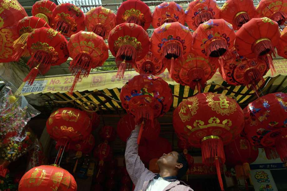 TOPSHOTS  A Cambodian man looks at Chinese Lunar New Year lanterns at a shop in Phnom Penh on February 8, 2013. The Chinese Lunar New Year, the most important of the traditional Chinese holidays will be celebrated from February 10 to 12. AFP PHOTO / TANG CHHIN SOTHYTANG CHHIN SOTHY/AFP/Getty Images Photo: TANG CHHIN SOTHY, AFP/Getty Images / AFP
