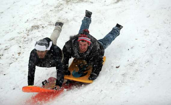 Sledders go over a small jump in Cummings Park during Friday's blizzard in Stamford, Conn., on February 8, 2013. Photo: Lindsay Perry / Stamford Advocate