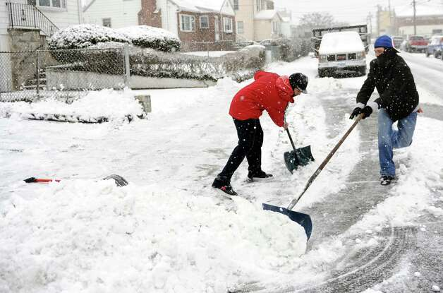 Jonathan Ruiz, left, and Jose Reyes, right, shovel a neighbor's driveway on Roosevelt Ave. in Stamford, Conn., during Friday's blizzard on February 8, 2013. Photo: Lindsay Perry / Stamford Advocate