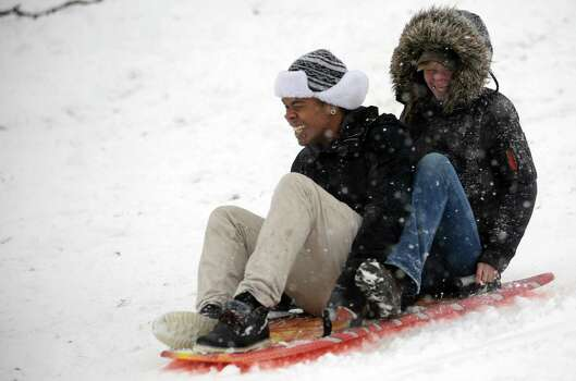 McLee Mathias, 18, and Carys Gray, 20, share a sled in Cummings Park during Friday's blizzard in Stamford, Conn., on February 8, 2013. Photo: Lindsay Perry / Stamford Advocate