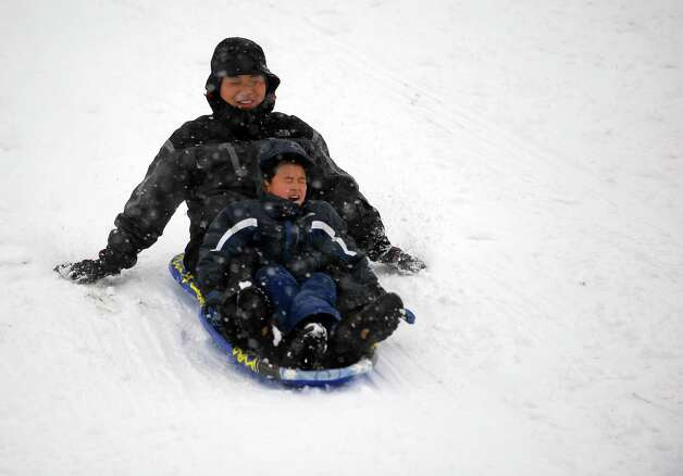 Jaehee You shares a sled with Caleb You, 6, in Cummings Park during Friday's blizzard in Stamford, Conn., on February 8, 2013. Photo: Lindsay Perry / Stamford Advocate