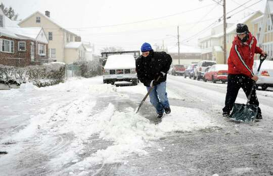 Jose Reyes, left, and Jonathan Ruiz, right, shovel a neighbor's driveway on Roosevelt Ave. in Stamford, Conn., during Friday's blizzard on February 8, 2013. Photo: Lindsay Perry / Stamford Advocate