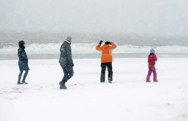 Jessica McManus went down to check out the weather at Penfield Beach in Fairfield, Conn. with her friends Gwen, Tom and Grace Noto. The snow and winds will continue to intensify over the next 24 hours. Coastal flooding is expected around the high tide mark of 9:45 pm tonight, Friday, Feb. 8, 2013. Photo: Cathy Zuraw / Connecticut Post