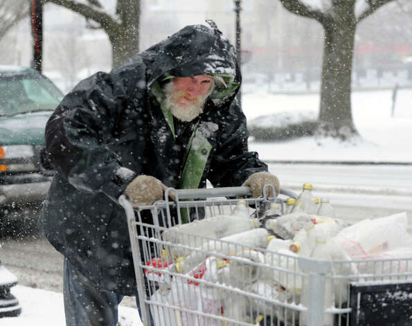 Chris Maloney pushes a shopping cart in the snow on Main Street in Danbury, Conn. Friday, Feb. 8, 2013. Photo: Carol Kaliff / The News-Times