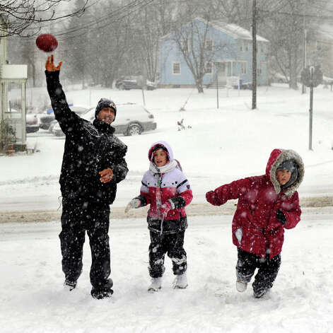 Dominick Craig throws a football for his daughter, Aaliyah, 8, center and Jaeden Fermin, 9, to catch on Mill Ridge Road in Danbury, Conn. during Friday's snowstorm, Feb. 8, 2013. Photo: Carol Kaliff / The News-Times