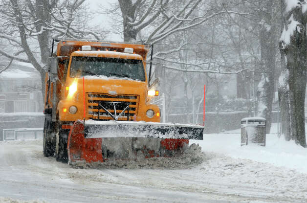 A town plow tries to keep up with the snow on the roads behind Milford City Hall as a major snow storm hits the region in Milford Conn. on Friday February 8, 2013. Photo: Christian Abraham / Connecticut Post