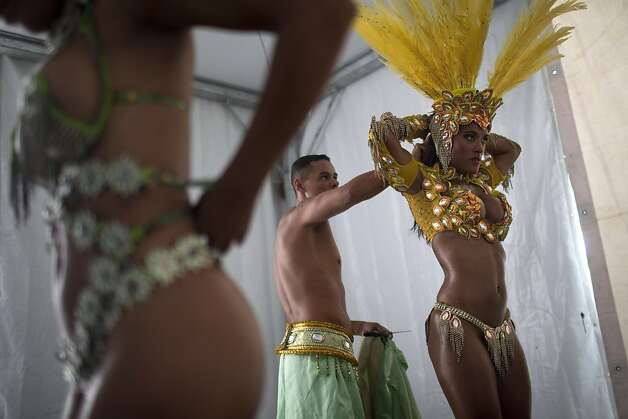 "Feather heads: Samba dancers get help dressing up for carnival parade rehearsals in Rio de Janeiro, although ""dressing up"" might be an overstatement. Photo: Felipe Dana, Associated Press"