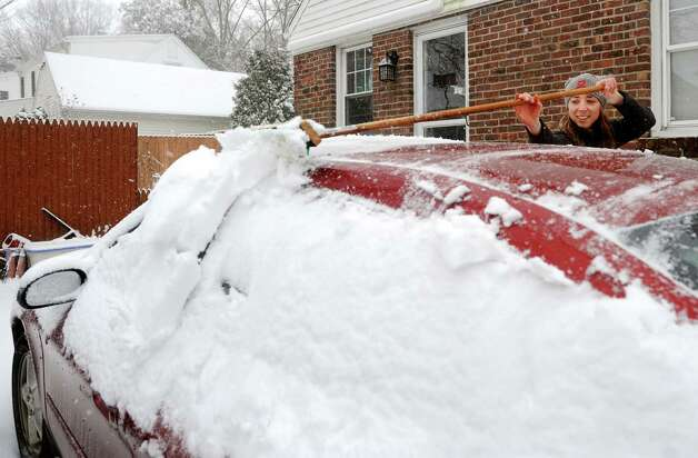 Veronica Swain brushes the snow off her car on South Pine Creek Rd. in Fairfield, Conn. on Friday, Feb. 8, 2013. The snow started around 7 a.m. and steadily increased into the afternoon. The storm is expected to continue overnight with high winds and a potential snowfall of 16 to 20 inches. Photo: Cathy Zuraw / Connecticut Post
