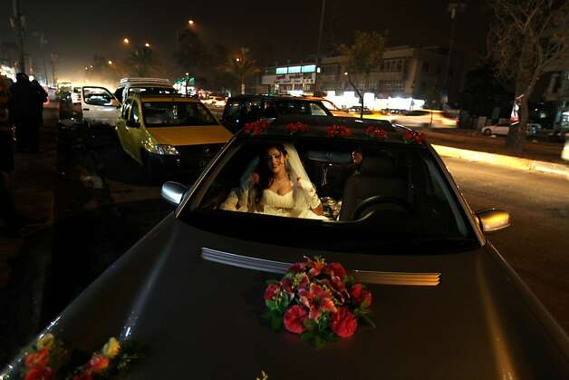 An Iraqi bride sits in her wedding car in Baghdad on February 7, 2013. Photo: Patrick Baz, AFP/Getty Images