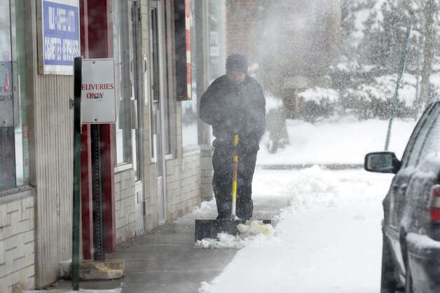 As snow from the roof blows downward Brian Porter, a worker with B&J Enterprises in Milford, shovels snow in front of a section of businesses along West River Street as a major snow storm hits the region in Milford Conn. on Friday February 8, 2013. Photo: Christian Abraham / Connecticut Post